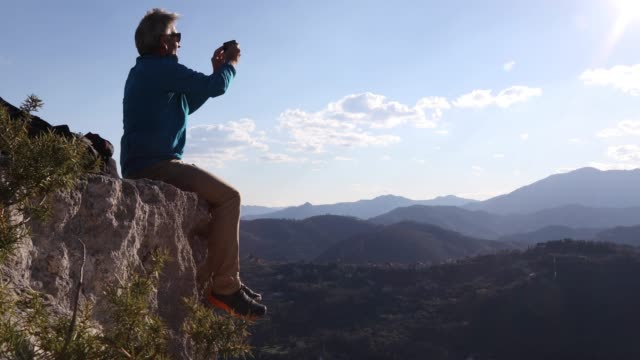 male hiker reaches rock crest above valley, mountains - see other clips from this shoot 56 stock videos & royalty-free footage
