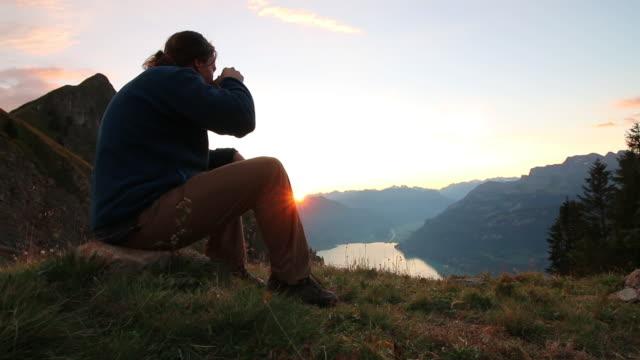 männliche wanderer entspannt über seen und bergen bei sonnenaufgang - sitzen stock-videos und b-roll-filmmaterial