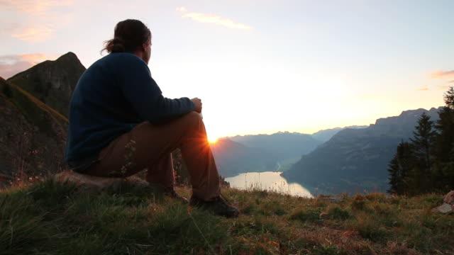 männliche wanderer entspannt über seen und bergen bei sonnenaufgang - nur junge männer stock-videos und b-roll-filmmaterial