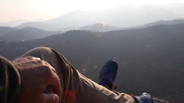 male hiker relaxes above mountain ranges at sunrise - legs crossed at ankle stock videos and b-roll footage
