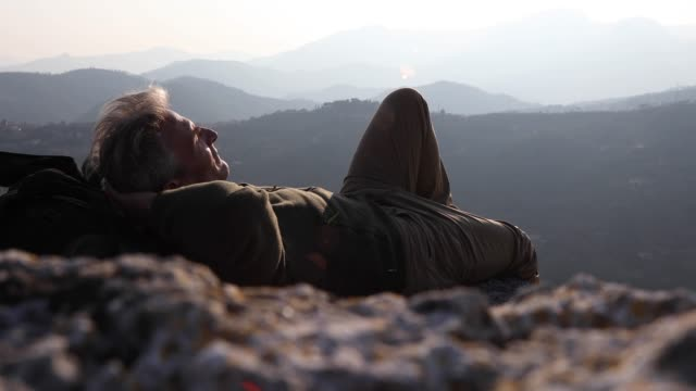 Male hiker relaxes above mountain ranges at sunrise