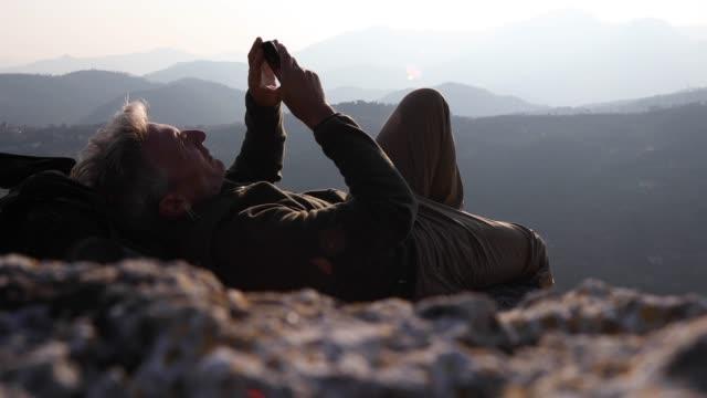 vídeos de stock, filmes e b-roll de alpinista masculina relaxa acima cordilheiras ao nascer do sol - áspero