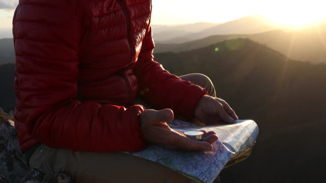 male hiker relaxes above mountaintops at sunrise - direction stock videos & royalty-free footage