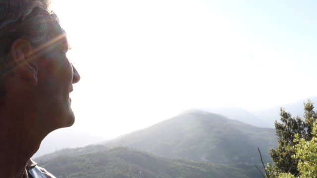 Male hiker relaxes above valley, drinks water