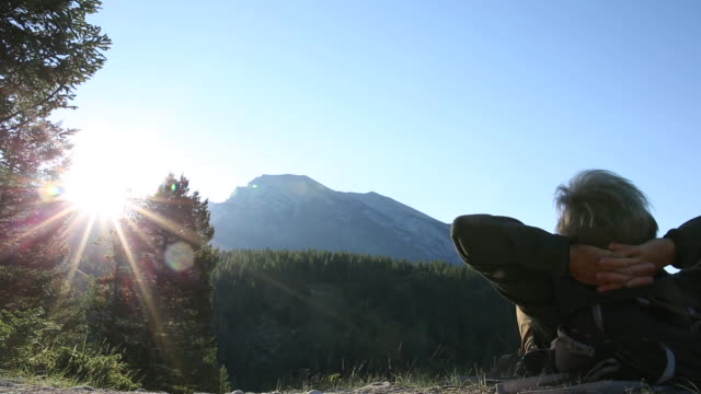 male hiker relaxes at edge of mountain trail, sunrise - hands behind head stock videos and b-roll footage