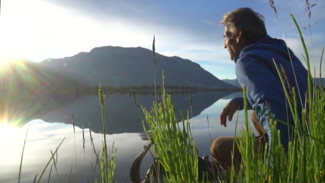 Male hiker relaxes at lake edge, watches sunrise over distant mountains