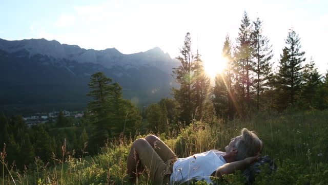 Male hiker relaxes in mountain meadow, sunrise
