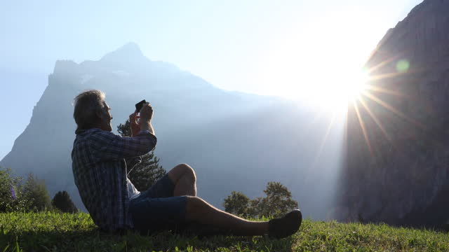 male hiker relaxes on meadow ridge crest, takes pic - shorts stock videos & royalty-free footage