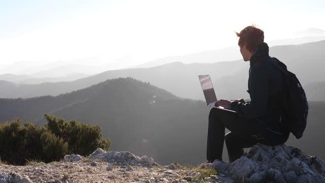 vídeos de stock e filmes b-roll de male hiker relaxes on mountain crest, using laptop computer - jaqueta jeans
