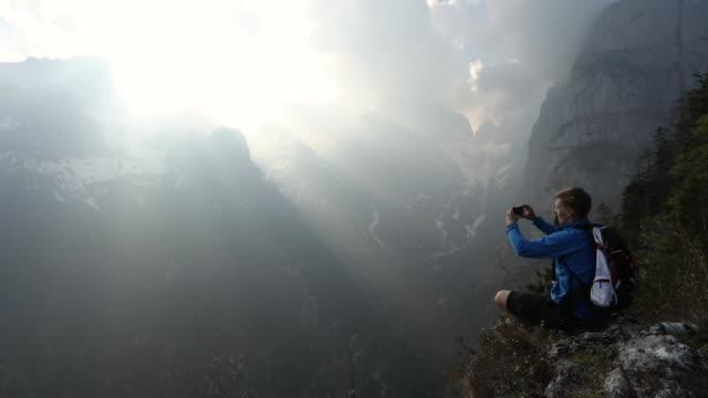 männliche wanderer entspannt am rand des abgrunds bei sonnenaufgang - exploration stock-videos und b-roll-filmmaterial