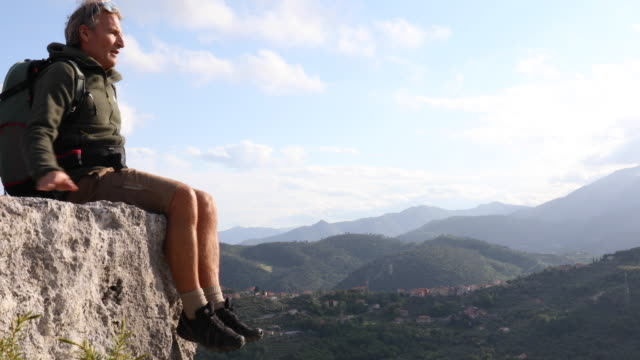 male hiker relaxes on rock crest, looks across hills - only mature men stock videos & royalty-free footage
