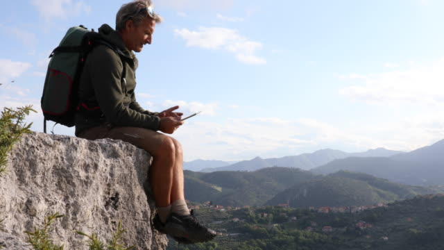 male hiker relaxes on rock crest, with digital tablet - rucksack stock videos & royalty-free footage