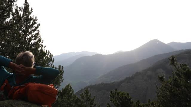 vídeos y material grabado en eventos de stock de male hiker relaxes on rock in mountain landscape - manos detrás de la cabeza
