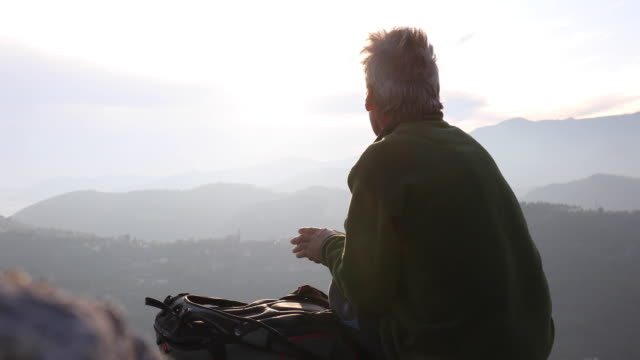 male hiker relaxes on rock summit at sunrise - see other clips from this shoot 56 stock videos & royalty-free footage