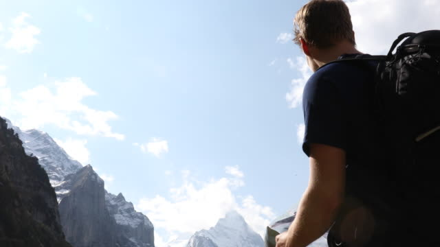 male hiker studies map before ascending into mountains - erholung stock-videos und b-roll-filmmaterial