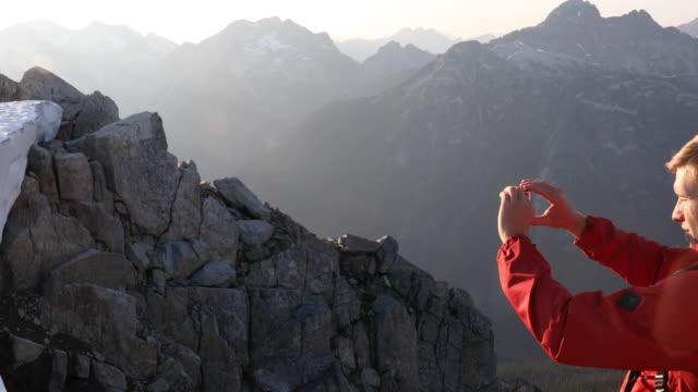 männlicher wanderer macht bild von bergszene bei sonnenaufgang - wintermantel stock-videos und b-roll-filmmaterial