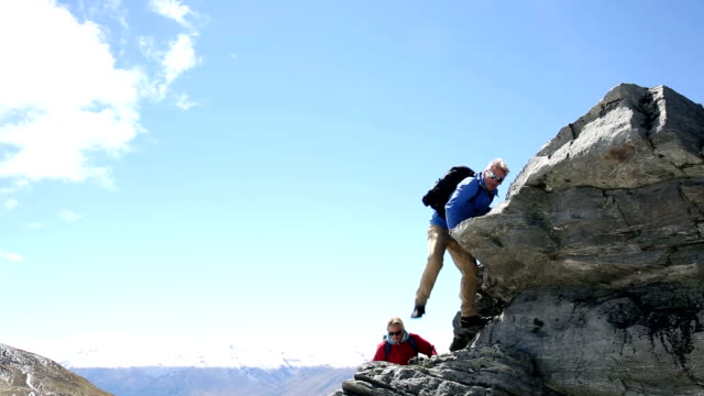 Male hiker traverses alpine ridge crest, in mountains