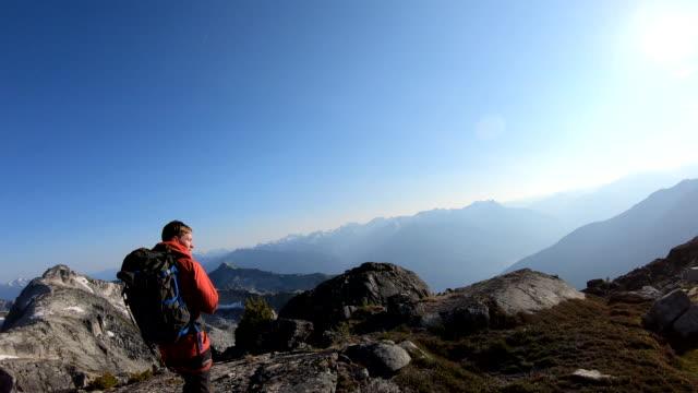 male hiker traverses mountain ridge crest at sunrise - ascentxmedia stock videos & royalty-free footage