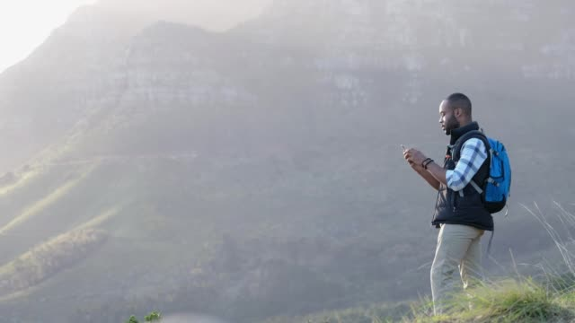male hiker using mobile phone in nature - remote location phone stock videos & royalty-free footage