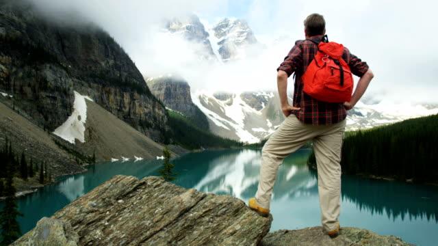 male hiker viewing cloud covered peaks lake moraine - red lake stock videos & royalty-free footage