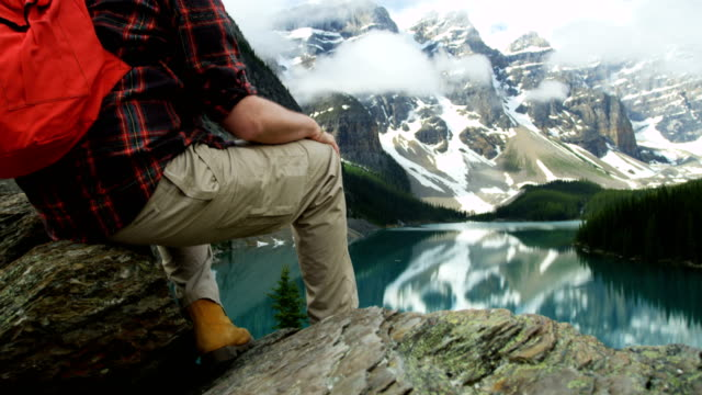 male hiker viewing turquoise lake moraine alberta canada - red lake stock videos & royalty-free footage