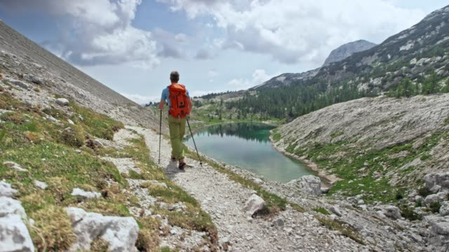 Male hiker walking on a gravel path above a mountain lake in sunshine