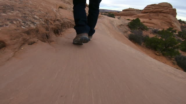 male hiker walking on red rocks, National Park, delicate arch, Arches National Park