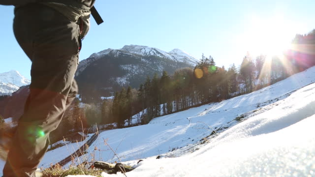 Male hiker walks above mountain road on icy slope towards distant mountain