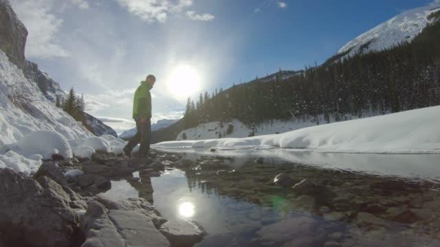 stockvideo's en b-roll-footage met mannelijke wandelaar wandelingen langs icy stream course, in de bergen - alleen oudere mannen