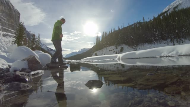 male hiker walks along icy stream course, in mountains - banff stock videos & royalty-free footage