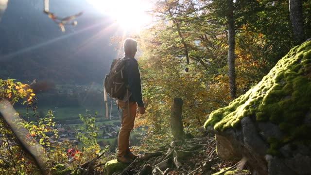 Male hiker walks through autumn forest above mountian village