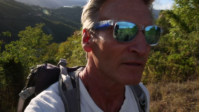 Male hiker walks through meadow and over hills, sunrise