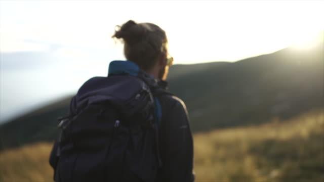 männlicher wanderer wandert bei sonnenuntergang mit rucksack unter berggipfel durch hohes gras - blondes haar stock-videos und b-roll-filmmaterial