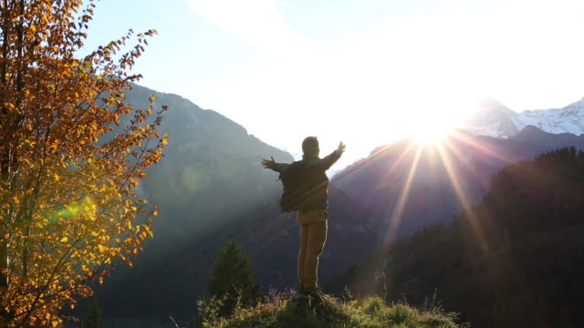 Male hiker walks to mountain crest, watches sunrise
