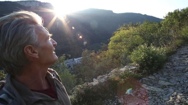 Male hiker walks up cobblestone path, hills distant, sunrise