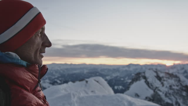 male hiker wearing knit hat on snowcapped mountain - austria stock videos & royalty-free footage