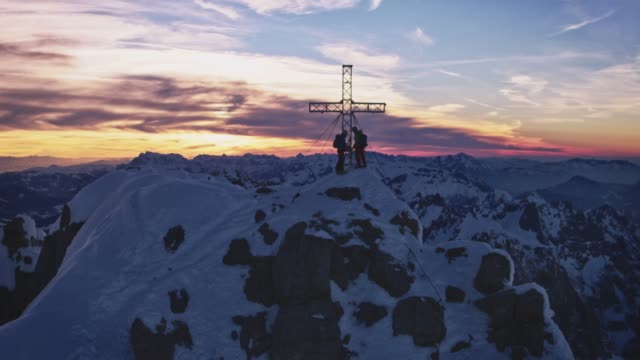 male hikers at summit cross during sunrise - austria stock videos & royalty-free footage