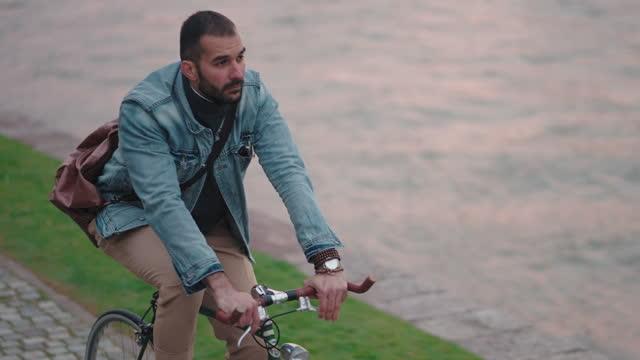 stockvideo's en b-roll-footage met mannelijke hipster, die de zonsondergang bewondert, terwijl het berijden van zijn groene retro fiets op een kade - rivier
