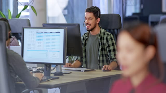 vídeos de stock e filmes b-roll de ld male hispanic call center customer service representative working at his desk in the call center - call center
