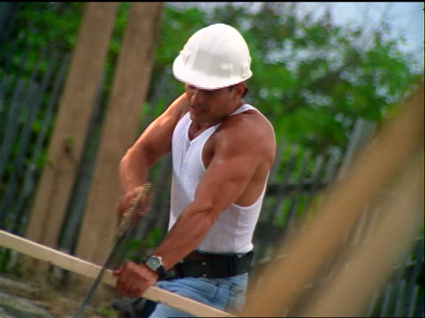 canted male hispanic construction worker sawing board + throwing hard hat into air / runs offscreen - baugerät stock-videos und b-roll-filmmaterial