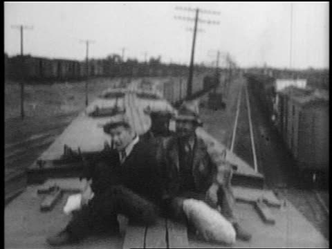 B/W 1935 3 male hobos sitting on top of moving train