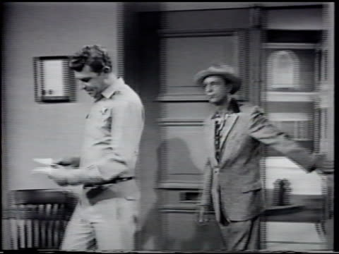 male holding clapboard in front of double doors andy walking into sheriff's office set followed by don knotts in civilian clothing asking about new... - fernsehserie stock-videos und b-roll-filmmaterial