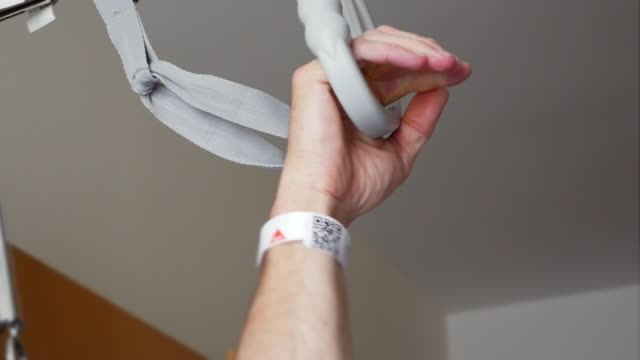 male hospital patient gripping trapeze bar - hospital bed stock videos & royalty-free footage