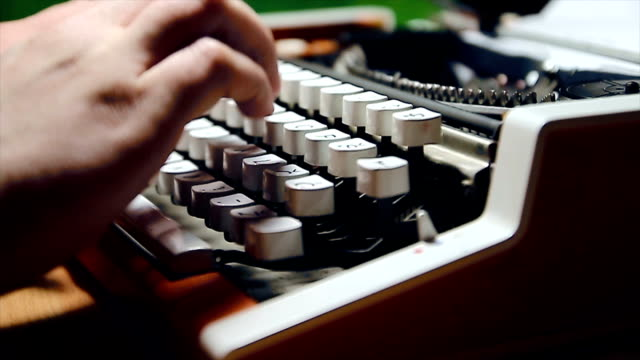 Male human hands write with an old fashion typewriter machine