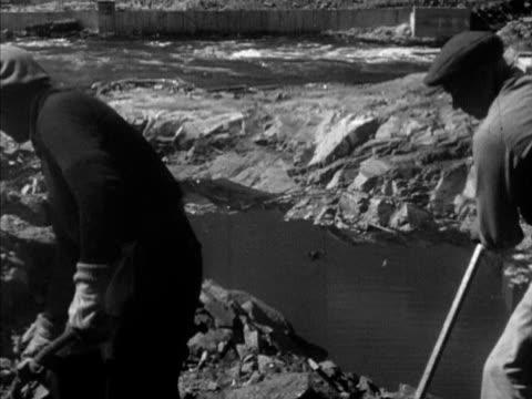 vídeos y material grabado en eventos de stock de male immigrants working on ottawa river dam project shoveling moving rocks w/ wheel barrows td ms men working w/ shovels amp jackhammer on steep... - río ottawa