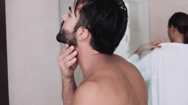 vídeos de stock e filmes b-roll de male in bathroom looking into mirror, female in shower - homem tomando banho