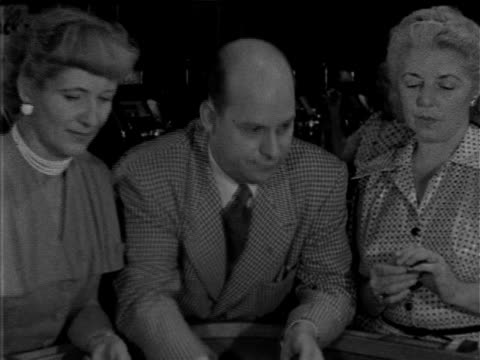 male in suit standing between two females, woman & man placing bets on table, watching unseen dice roll, slot machine along wall bg. gambling,... - 1952 stock videos & royalty-free footage