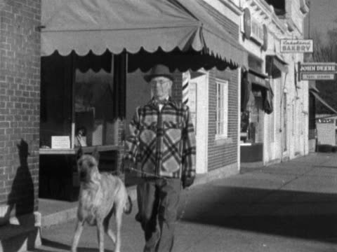 Male in top hat wearing jacket walking Great Dane dog along city street WI aka German Mastiff Danish Hound