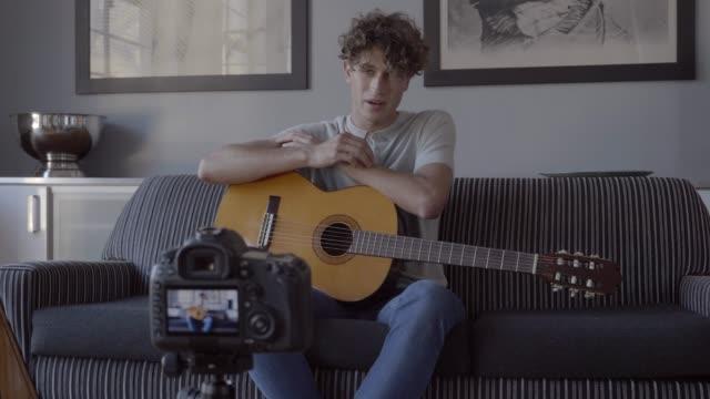 vídeos de stock e filmes b-roll de male influencer playing guitar while making video tutorial - geração z