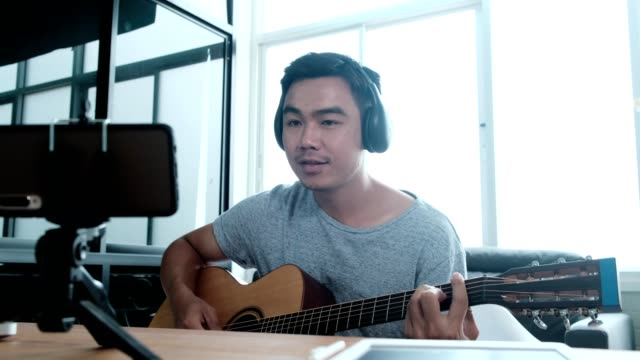 male influencer playing guitar while making video tutorial,vlogger recording guitar lesson on video camera - individuality stock videos & royalty-free footage